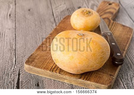 Round yellow turnip and a knife on a cutting board on a gray wooden table.