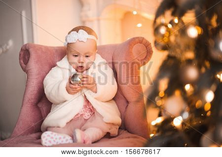 Baby girl 1 year old holding Christmas ball sitting on pink stylish chair under Christmas tree in room. Holiday season.