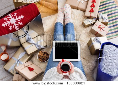 Christmas online shopping top view. Female buyer touch black screen of tablet, copy space. Woman has coffee, buys presents, prepare to xmas eve, sit near gifts boxes and packages. Winter holiday sales