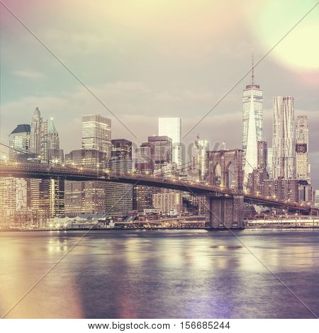 Vintage style view of  Brooklyn Bridge and Lower Manhattan skyline in New York City with city illumination, USA