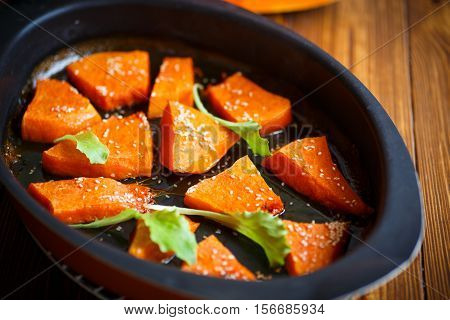 Pumpkin baked with honey and sesame seeds on a baking sheet