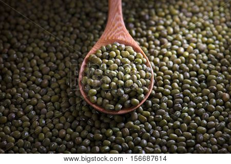 Mung beans in wooden spoon on mung beans background.
