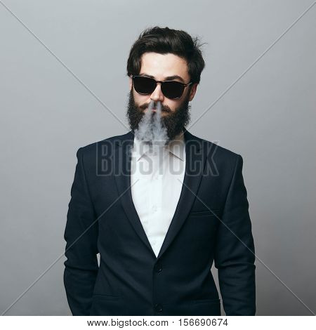 Rugged and manly. Confident young bearded man wearing a black suit an sunglasses looking confidently at camera and exhaling smoke
