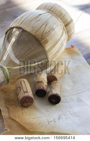 flask of red wine with some old corks