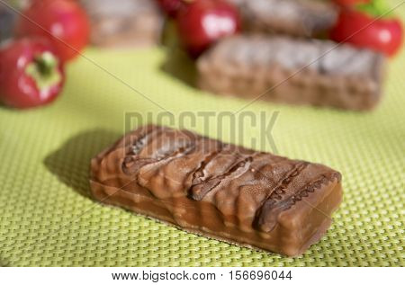 chocolate snack and hot chilli peppers on green background