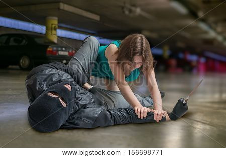 Self defense concept. Young woman is fighting with mugger or thief.