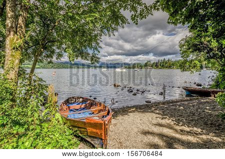 Dilapidated rowing boat pulled up onto sandy shore of Lake Windermere in the English Lake District, Cumbria.