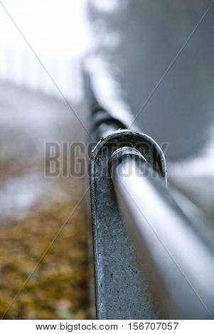 the iron railing along the country road.