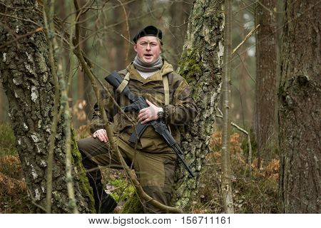 a military man in the woods with an assault rifle autumn forest with no leaves green form