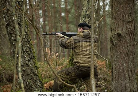 a military man in the woods with a Kalashnikov assault rifle autumn forest with no leaves green form No face.