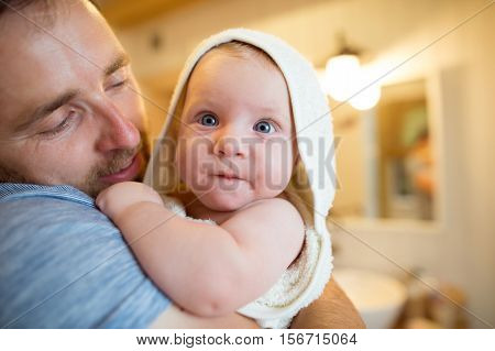 Young father holding in his arms his son wrapped in towel after bathing him. Close up.