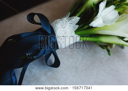A Beautiful Bouquet Of Lilies With Blue Silk Ribbon