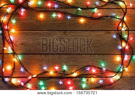 Christmas lights background. Holiday shiny garland frame top view on brown wooden planks surface. Xmas tree decorations, winter holidays illumination