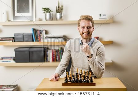 Portrait of a young man is playing a chess and looking at the camera.