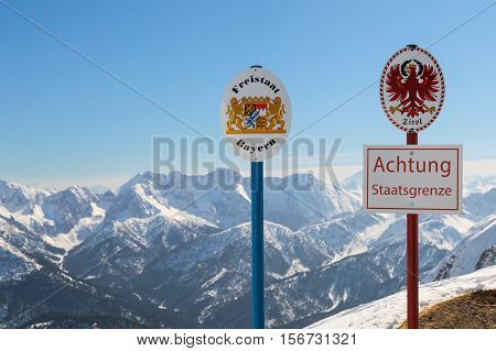 State boundary between Germany and Austria on top of Alpine mountain ridge. Sgnboards with the coat of arms of free state Bavaria and Tyrol and words