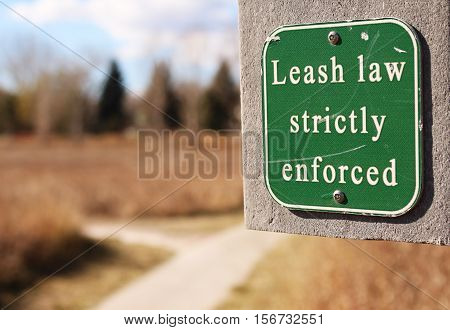 Sign along walking path warns that laws regarding dog leashes are strictly enforced.