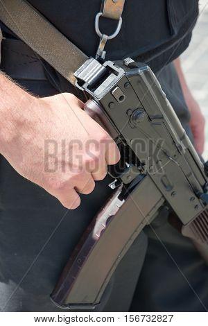 Ukrainian soldier with machine gun. The hand on the machine gun close-up.