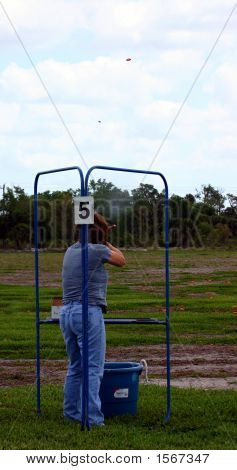Female Skeet Clay Shooter In Action