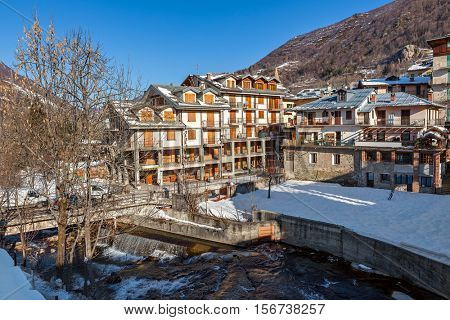 Stream and houses in Limone Piemonte covered with snow - small alpine town, popular winter resort in Italy.