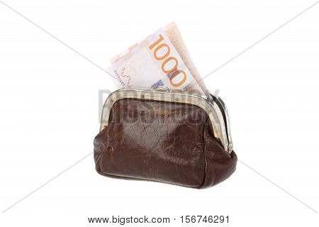 One brown purse with a 1000 Swedish krona banknote inside isolated on white background.