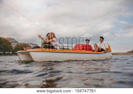 Shot of young friends sitting in pedal boat enjoying holidays. Group of people boating in the lake taking selfie.