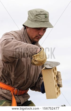 Tyumen, Russia - May 23, 2008: Bricklayer works on construction of 18 floor brick residental house at intersection of streets of Gercena and Chelyuskincev. Bricklayer behind work