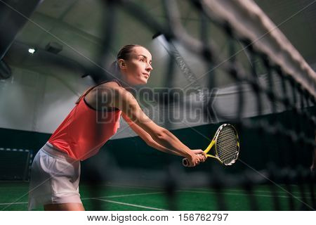My favorite activity. Pleasant concentrated beautiful woman holding racket and training while playing tennis
