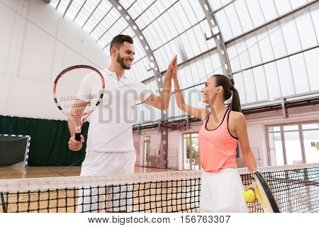 Thank you for set. Positive professioanl tennis players standing near net and giving high five while resting after playing tennis