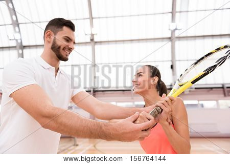 Diligent student. Pleasant smiling beautiful woman holding racket while training with instructor and going to play tennis