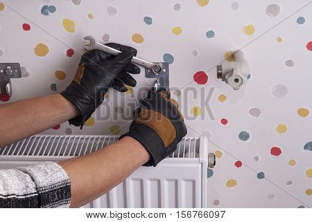 plumber installs heating radiator brackets to the wall