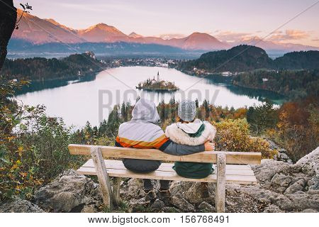 Lovers travel Europe. Couple in love looking on Bled Lake. Autumn or Winter in Slovenia Europe. Top view on Island with Catholic Church in Bled Lake with Castle and Mountains in Background.