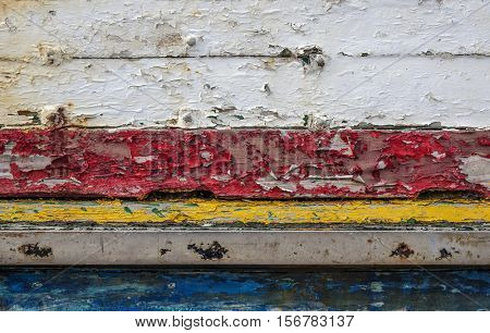Background detail of old boat with red, yellow, blue and white peeling paint