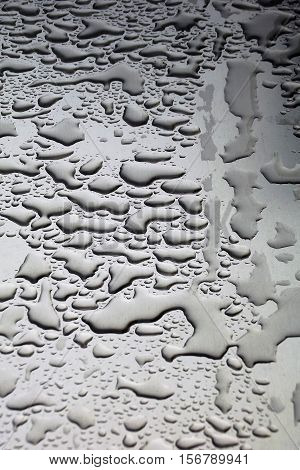 Water droplets on aluminium surface after rainfall. Vertical 3:2 format from above.