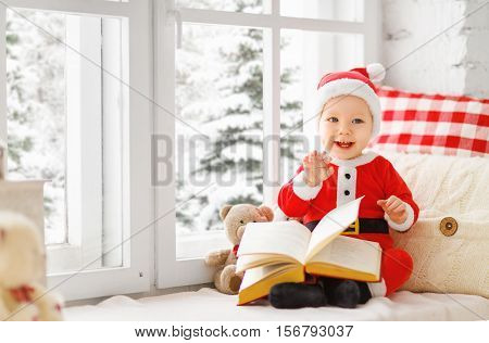 happy baby dressed as Santa Claus sitting on window of house in winter on Christmas