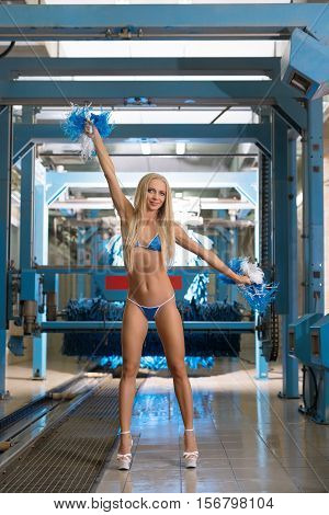 At car wash. Beautiful blonde posing in bikini with pom-poms