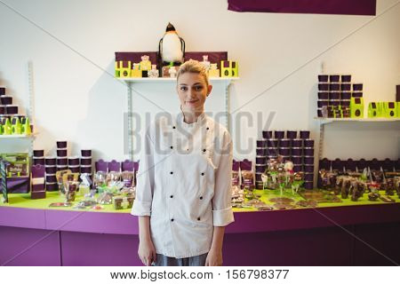 Portrait of worker standing next to chocolate display in cake shop
