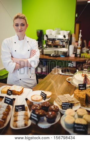 Portrait of worker standing at chocolate counter in cake shop