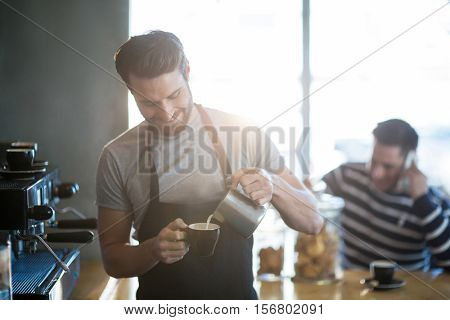 Smiling waiter making cup of coffee at counter in cafe