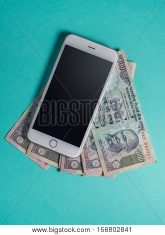 A smart phone with Indian currency notes. view from top.