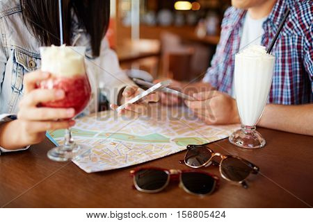 Travelers using map and mobile navigation to plan route