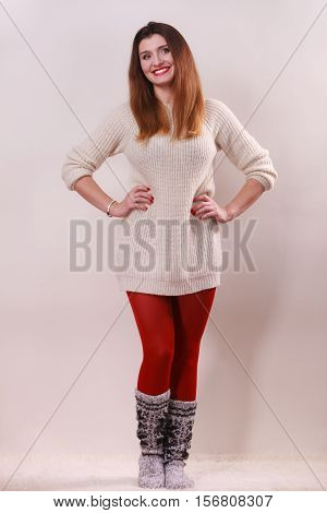 Winter fashion. Happy young woman in full length wearing fashionable wintertime clothes woolen warm sweater socks and red tights