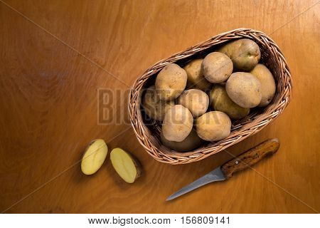 Potatoes in wicker basket on wooden table.Useful as a food background