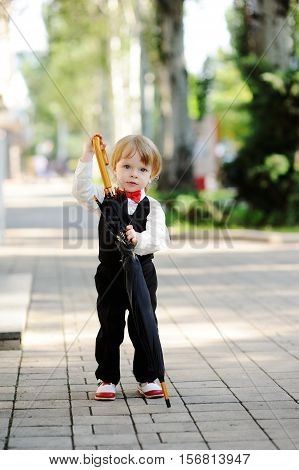cute baby boy in a red bow tie is holding a large black umbrella