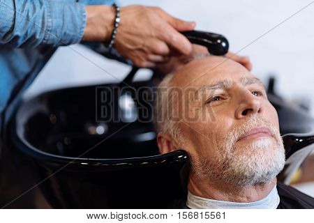 Enjoying service. Close up portrait of senior bearded man sitting in barber shop while professional stuff washing his hair.