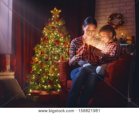 Merry Christmas and Happy Holidays! Mother and child girl with magic gift box on Christmas. Christmas family traditions.