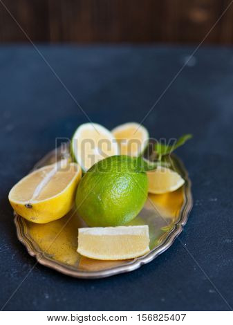 Juicy ripe citrus on a silver tray. Lime and lemon. Healthy eating concept
