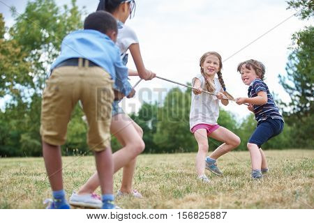 Happy group of kids playing tug of war