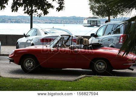 SIRMIONE ITALY - MAY 5 2016: Couple in vintage red cabriolet Alfa Romeo Giulietta Spider in Sirmione Garda Lake Italy