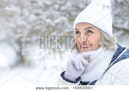 Portrait of smiling senior woman in a snow-covered winter park looking ath the distance