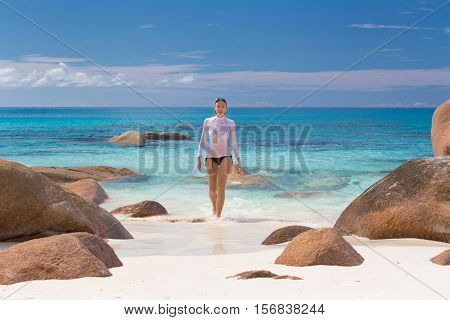 Woman wearing stylish bikini and lycra top enjoying swimming and snorkeling at amazing Anse Lazio beach on Praslin Island, Seychelles. Summer vacations on picture perfect tropical beach concept.